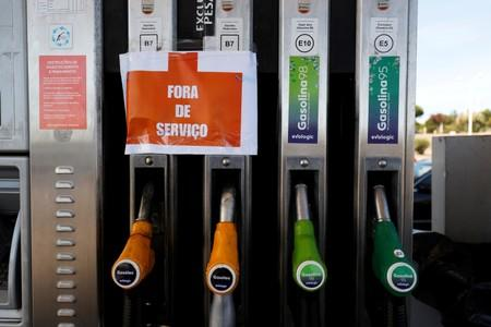 "FILE PHOTO: A sign reading ""Out of service"" hangs on fuel pumps at a petrol station during a fuel strike, near Lisbon"