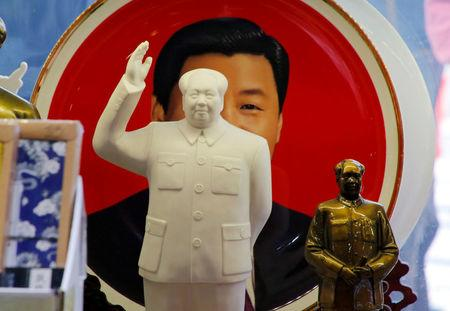 FILE PHOTO: Sculptures of the late Chinese Chairman Mao Zedong are placed in front of a souvenir plate featuring a portrait of Chinese President Xi Jinping at a shop next to Tiananmen Square in Beijing, China, March 1, 2018.  REUTERS/Jason Lee/File Photo