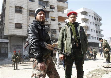 A member of Syria's armed opposition forces (L) stands next to a soldier from the forces loyal to Syria's President Bashar al-Assad in Babila town, southeast Damascus February 17, 2014, after a local ceasefire agreement was reached. Picture taken during a guided tour by the Syrian Army. REUTERS/Khaled al-Hariri
