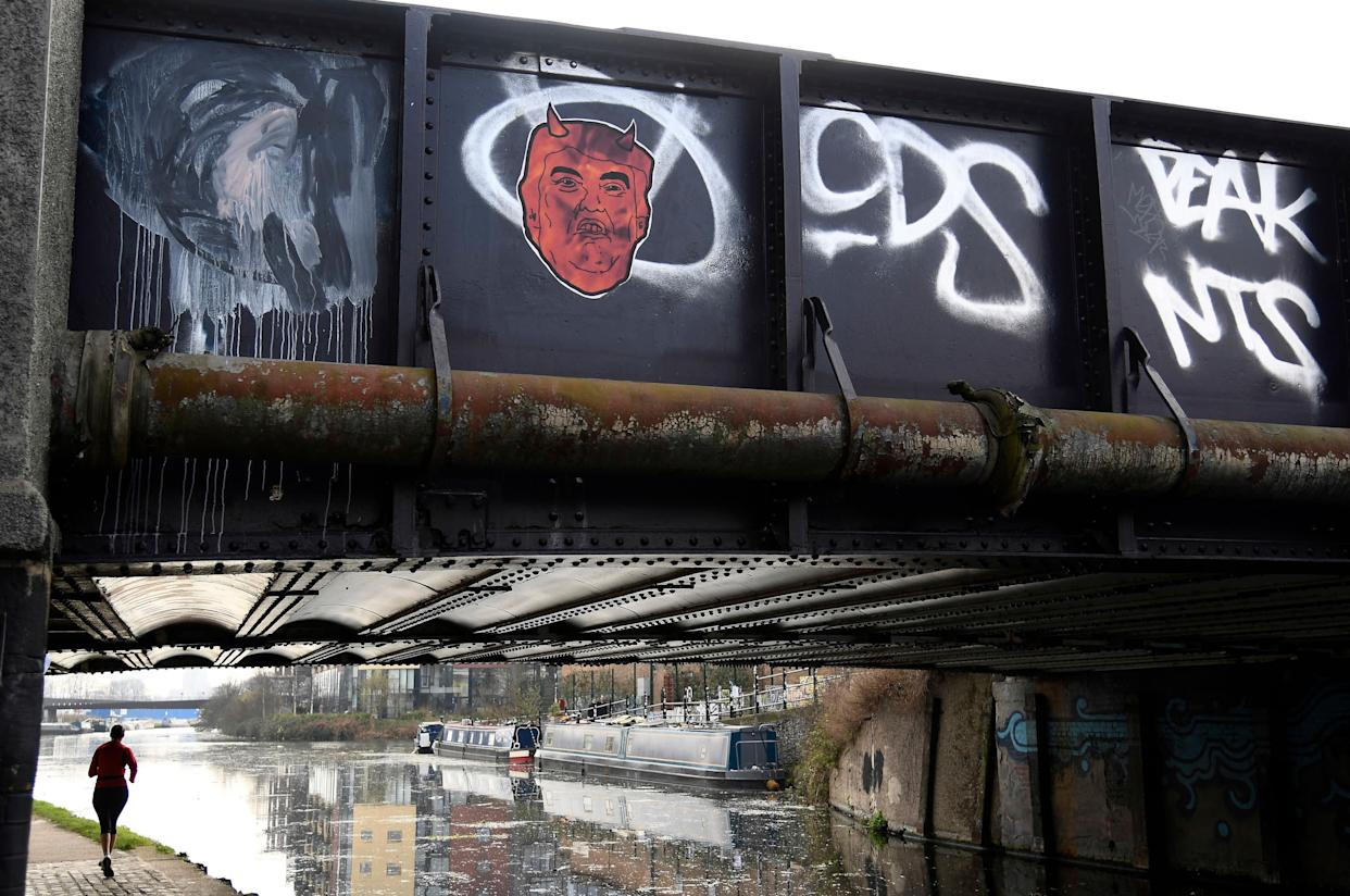 A woman runs along a towpath near graffiti depicting U.S. President Donald Trump on a canal bridge in east London, Britain, February 18, 2017.