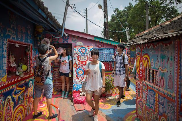 TAICHUNG, TAIWAN - JULY 22: Tourists visit the Rainbow Military Dependents' Village on July 22, 2013 in Taichung in Taiwan. The village, one of more than 800 settlements built for retired Chinese soldiers after World war II, has become a distinctive tourist attraction after a retired soldier, Huang Yung-fu, painted hundreds of brightly coloured murals. (Photo by Lam Yik Fei/Getty Images)