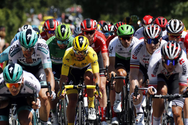 The pack rides with France's Julian Alaphilippe wearing the overall leader's yellow jersey during the tenth stage of the Tour de France cycling race over 217 kilometers (135 miles) with start in Saint-Flour and finish in Albi, France, Monday, July 15, 2019. (AP Photo/ Christophe Ena)