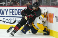 Carolina Hurricanes center Jordan Staal (11) falls on Nashville Predators center Yakov Trenin (13) during the first period in Game 1 of an NHL hockey Stanley Cup first-round playoff series in Raleigh, N.C., Monday, May 17, 2021. (AP Photo/Gerry Broome)