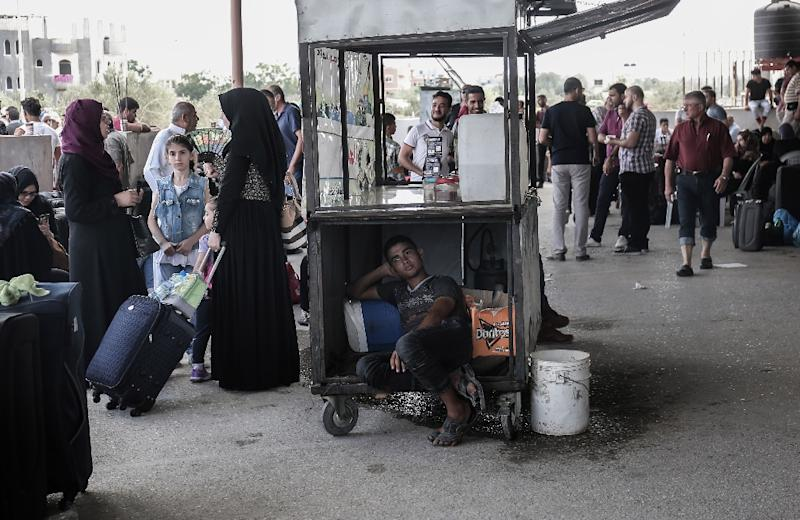 Palestinians wait for travel permits to cross into Egypt through the Rafah border crossing after it was briefly opened on August 16, 2017