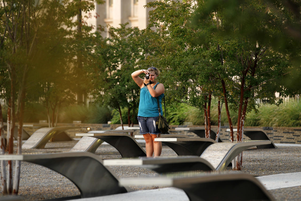 A visitor takes pictures at the permanent outdoor Pentagon Memorial in Arlington Va. The 184 stone benches each bear the name of a person who died Sept. 11, 2001, in the terrorist attack on the Pentagon. Together they comprise the permanent outdoor Pentagon Memorial, created to honor family members and friends killed both in the building and on American Airlines Flight 77. The Pentagon was the first of the three attack sites to open an official memorial. It was dedicated Sept. 11, 2008, and is open 24 hours a day, 365 days a year. (AP Photo/Jose Luis Magana)