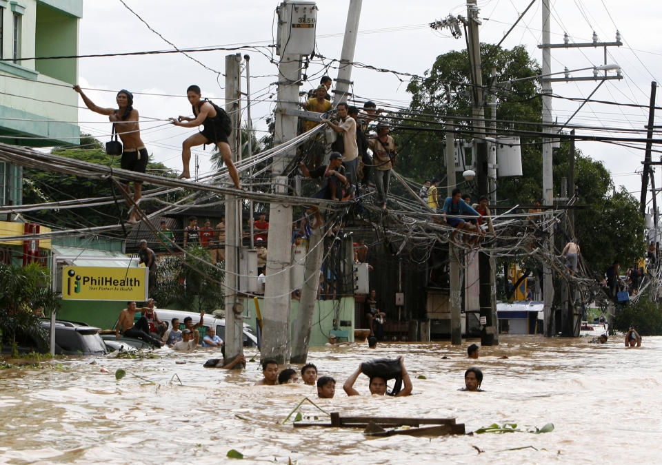 FILE PHOTO: Residents stand on electric wires to stay on high ground while others wade in neck-deep flood waters caused by Typhoon Ondoy in Cainta Rizal on September 27, 2009. (Source: REUTERS/Erik de Castro)