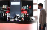 An employee looks on as a robotic arm serves a Campari Soda long drink in Zurich