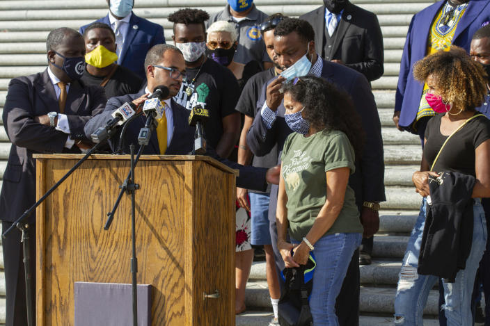 """Attorney Ron Haley adjusts the microphone at the podium for Mona Hardin, center, mother of Ronald Greene, as she approaches to speak at a news conference outside the Louisiana State Capitol in Baton Rouge, La., Wednesday, Oct. 7, 2020. Attorney Lee Merritt stands directly behind Hardin. Greene died following a police chase in Louisiana in 2019, and his death is now under federal investigation. Greene's family filed a federal wrongful-death lawsuit in May alleging troopers """"brutalized"""" Greene, used a stun gun on him three times and """"left him beaten, bloodied and in cardiac arrest,"""" before covering up his actual cause of death. (AP Photo/Dorthy Ray)"""