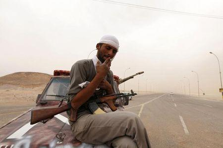 A rebel fighter from the city of Misrata smokes a cigarette as he stands guard on the road to the airport in the southern Libyan city of Sabha
