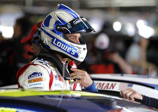 Jimmie Johnson talks to a crew member before practice for Sunday's NASCAR Sprint Cup series Coca-Cola 600 auto race at Charlotte Motor Speedway in Concord, N.C., Thursday, May 22, 2014. (AP Photo/Terry Renna)