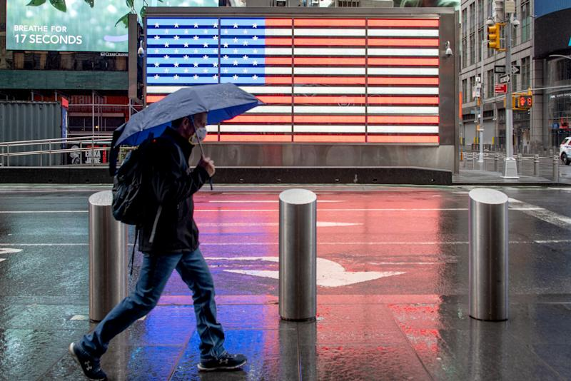 NEW YORK, NEW YORK - MAY 06: A man wearing a mask walks with an umbrella in Times Square near the American Flag amid the coronavirus pandemic on May 6, 2020 in New York City. COVID-19 has spread to most countries around the world, claiming over 263,000 lives with over 3.8 million cases. (Photo by Alexi Rosenfeld/Getty Images)