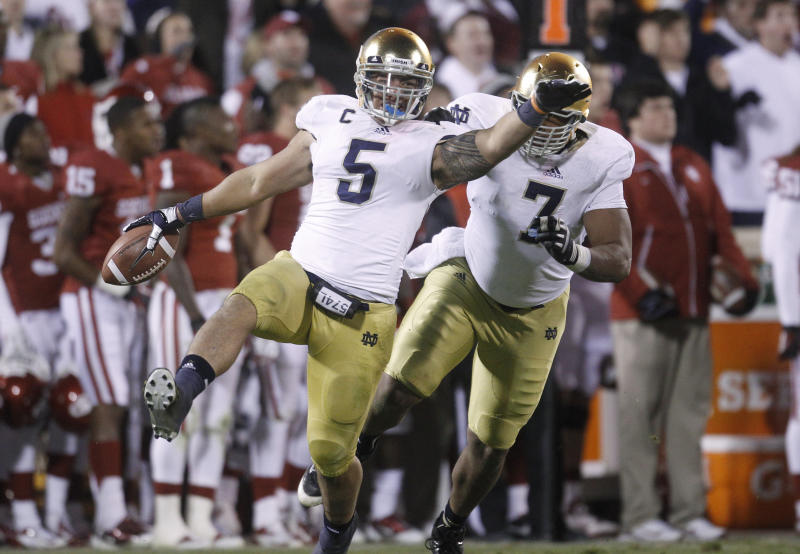 Notre Dame linebacker Manti Te'o (5)celebrates with teammate Stephon Tuitt (7) after an interception against Oklahoma in the fourth quarter of an NCAA college football game in Norman, Okla., Saturday, Oct. 27, 2012. (AP Photo/Sue Ogrocki)