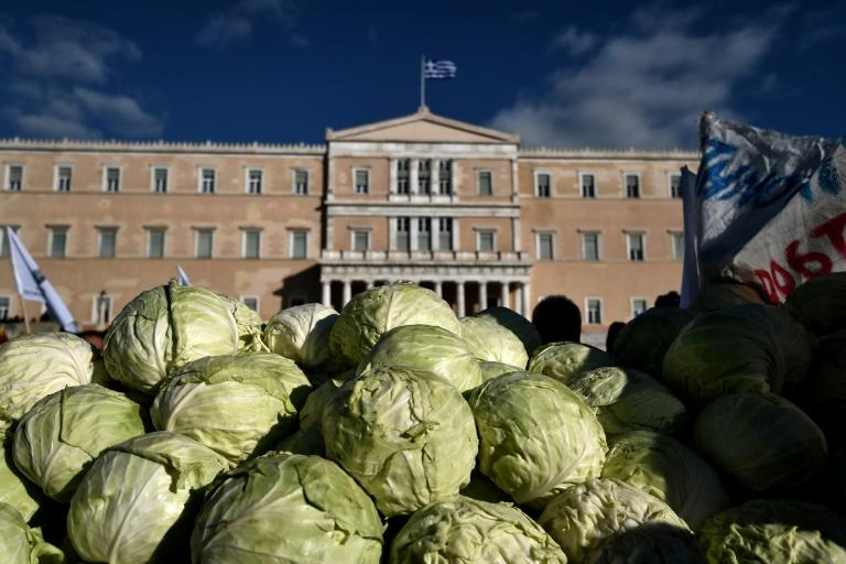 Greek farmers dump cabbages outside parliament on February 14, 2017 during an anti-austerity demonstration