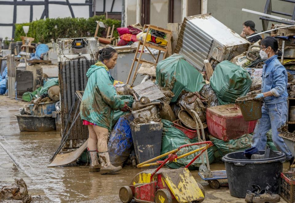 People clean their homes from mud and debris in Bad Neuenahr-Ahrweiler, Germany, Saturday, July 17, 2021. Due to strong rainfall, the Ahr river went over its banks and flooded big parts of the town. (AP Photo/Michael Probst)