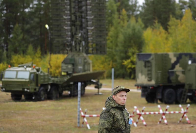 """A Russian soldier stands in front of a Nebo-M radar deployed in a forest, during a military exercises on training ground """"Telemba"""", about 80 kilometers (50 miles ) north of the city of Chita during the military exercises Vostok 2018 in Eastern Siberia, Russia, Wednesday, Sept. 12, 2018. Hundreds of thousands Russian troops swept across Siberia on Tuesday in the nation's largest ever war games also joined by China — a powerful show of burgeoning military ties between Moscow and Beijing amid their tensions with the U.S. (AP Photo/Sergei Grits)"""