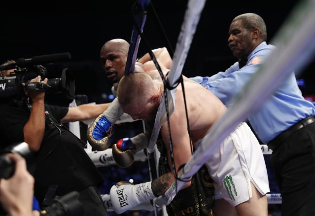 <p>Floyd Mayweather Jr. in action with Conor McGregor as referee Robert Byrd looks on REUTERS/Steve Marcus </p>