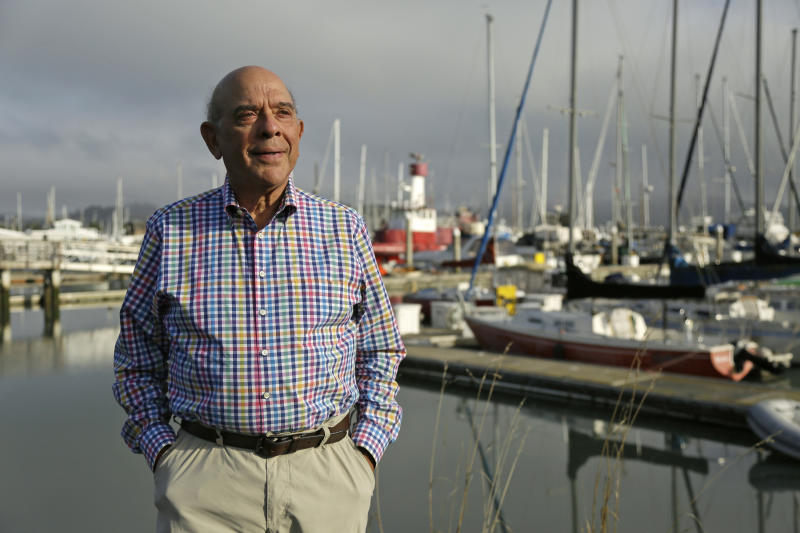 In this Tuesday, Sept. 25, 2018, photo Gerry Goldsholle poses for a photo by a harbor outside his office in Sausalito, Calif. Goldsholle just celebrated his 78th birthday, and he's still working. Close to one in five Americans who's 65 or older is still working, the highest percentage in more than half a century. (AP Photo/Eric Risberg)