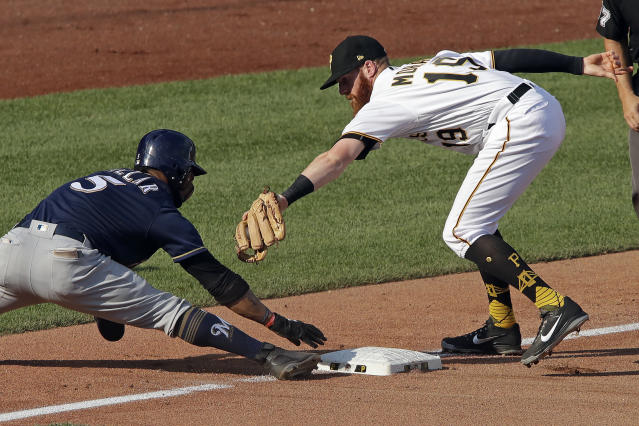 Milwaukee Brewers' Jonathan Villar (5) can't hold the bag as Pittsburgh Pirates third baseman Colin Moran (19) reaches to make the tag, after going first to third on a single by Hernan Perez in the seventh inning of the second baseball game of a doubleheader in Pittsburgh, Saturday, July 14, 2018. (AP Photo/Gene J. Puskar)