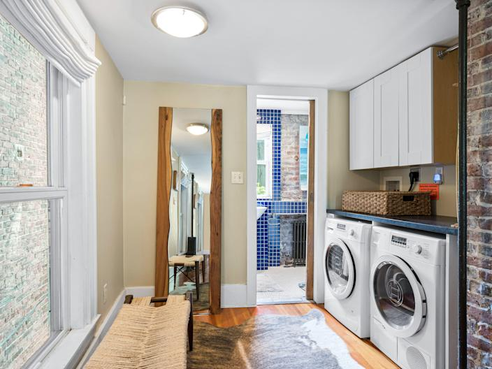 A washer and dryer on the right and windows on the left.