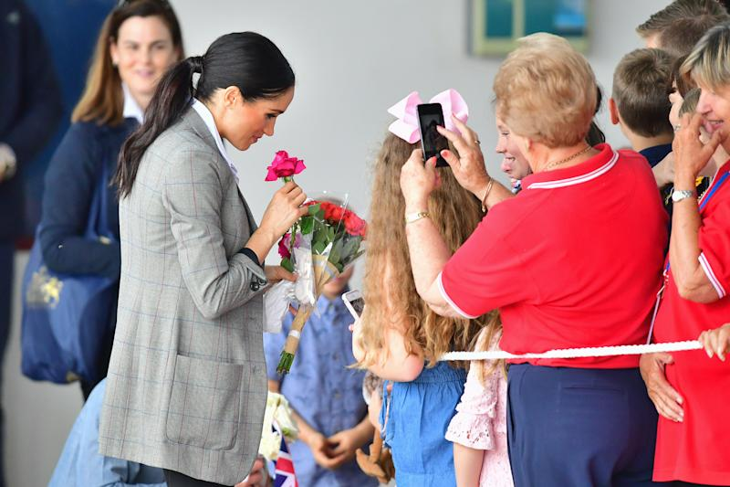 Meghan takes a moment to appreciate some flowers given to her. Photo: Getty, meghan markle prince harry dubbo, meghan markle prince harry australia, meghan markle serena williams jacket, meghan markle pregnant