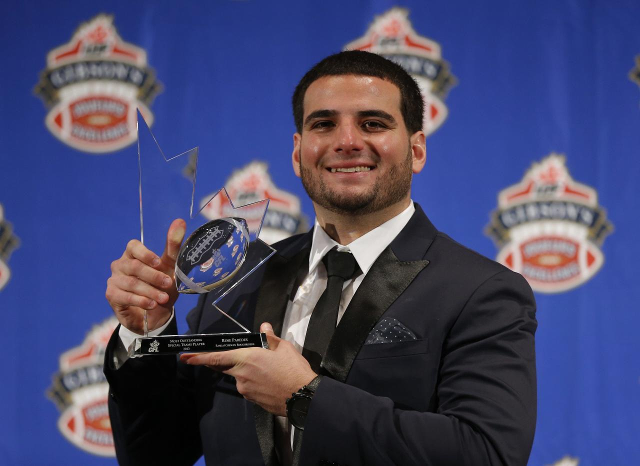 Rene Paredes of the Calgary Stampeders holds the trophy after being named the CFL's Most Outstanding Special Teams Player at the CFL Player Awards in Regina, November 21, 2013. Regina, Saskatchewan, November 21, 2013. REUTERS/Todd Korol (CANADA)