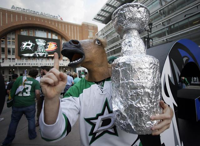 Alex Churchman of Rowlett, Texas, wears a horse head costume piece as he walks around the plaza motivating fans before a first-round NHL hockey Stanley Cup playoff series game against the Anaheim Ducks, Monday, April 21, 2014, in Dallas. (AP Photo/Tony Gutierrez)