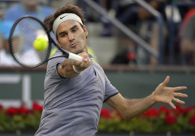 Roger Federer, of Switzerland, returns a shot against Tommy Haas, of Germany, during a match at the BNP Paribas Open tennis tournament on Wednesday, March 12, 2014, in Indian Wells, Calif. (AP Photo/Mark J. Terrill)