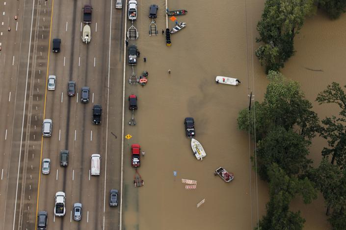 Vehicles sit on a flooded portion of Interstate 10.