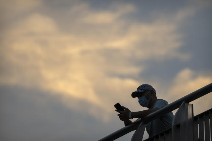A man wearing a face mask to protect against COVID-19 stands on a pedestrian bridge in the central business district in Beijing, Thursday, Sept. 16, 2021. China on Thursday reported several dozen additional locally-transmitted cases of coronavirus as it works to contain an outbreak in the eastern province of Fujian. (AP Photo/Mark Schiefelbein)