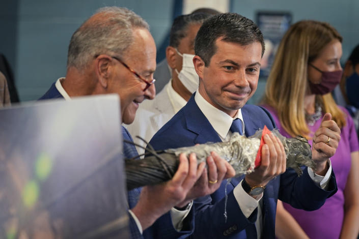 Secretary of Transportation Pete Buttigieg, right, and Sen. Chuck Schumer, D-N.Y., hold a decaying piece of a rail tunnel while they speak during a news conference in New York, Monday, June 28, 2021. Buttigieg toured the century-old rail tunnel connecting New York and New Jersey as a long-delayed project to build a new tunnel gains steam. (AP Photo/Seth Wenig)