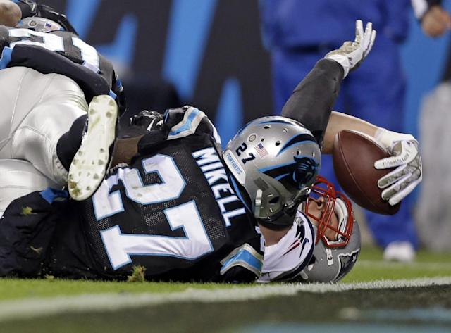 New England Patriots' Rob Gronkowski, right, stretches the ball over the goal line for a touchdown as Carolina Panthers' Quintin Mikell, left, defends during the second half of an NFL football game in Charlotte, N.C., Monday, Nov. 18, 2013. (AP Photo/Gerry Broome)