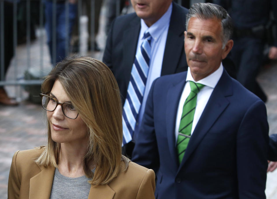 Lori Loughlin, left, leaves as her husband Mossimo Giannulli, right, trails behind her outside of the John Joseph Moakley United States Courthouse in Boston on April 3, 2019. (Photo by Jessica Rinaldi/The Boston Globe via Getty Images)
