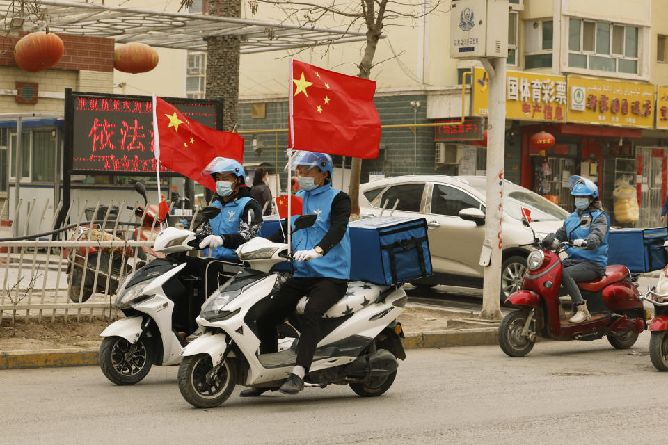 Delivery workers flying Chinese national flags ride around in a convoy to promote their services in Shule county in northwestern China's Xinjiang Uyghur Autonomous Region on March 20, 2021. Four years after Beijing's brutal crackdown on largely Muslim minorities native to Xinjiang, Chinese authorities are dialing back the region's high-tech police state and stepping up tourism. But even as a sense of normality returns, fear remains, hidden but pervasive. (AP Photo/Ng Han Guan)
