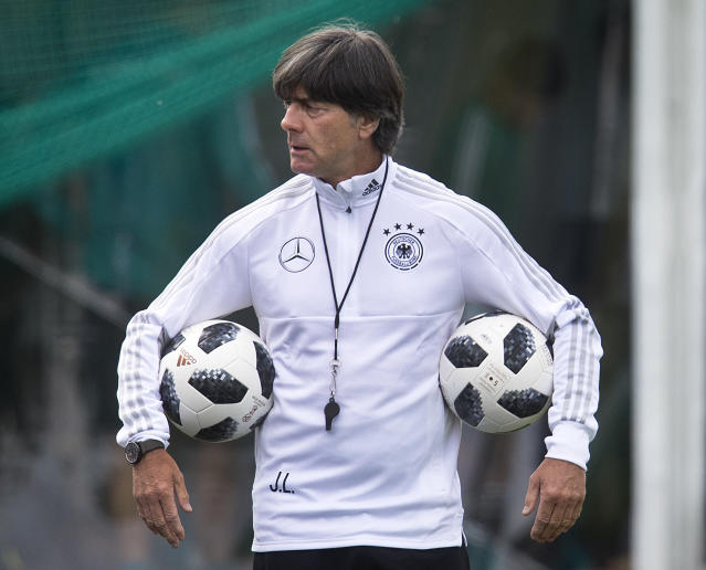 Coach of German national soccer team Joachim Loew carries two balls during a training session at the 2018 soccer World Cup in Vatutinki near Moscow, Russia, Thursday, June 14, 2018. (AP Photo/Michael Probst)