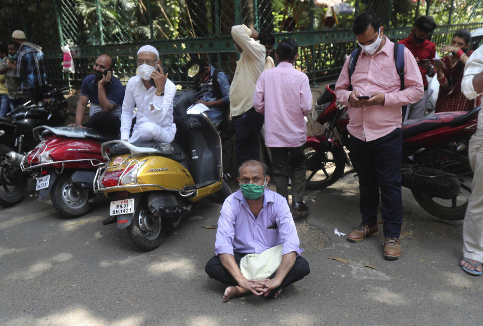 A man wearing mask sits on the road as he waits his turn for COVID-19 test outside a court in Mumbai, India, Monday, April 5, 2021. India reported its biggest single-day spike in confirmed coronavirus cases since the pandemic began Monday, and officials in the hard-hit state home to Mumbai are returning to the closure of some businesses and places of worship in a bid to slow the spread. (AP Photo/Rafiq Maqbool)