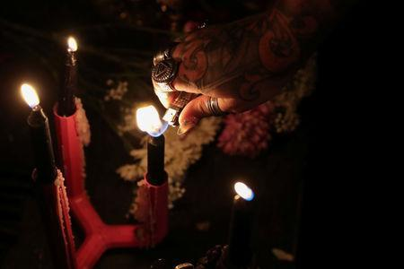 A self-proclaimed witch lights a candle before a ceremony hexing U.S. Supreme Court Justice Brett Kavanaugh at Catland Books in Brooklyn, New York, U.S., October 20, 2018. REUTERS/Shannon Stapleton