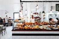 """<p><strong>What's the vibe?</strong><br> It's easy to understand why Instagram influencers flock to Tatte, with its unmistakably <a href=""""https://www.cntraveler.com/gallery/best-bakeries-in-paris?mbid=synd_yahoo_rss"""" rel=""""nofollow noopener"""" target=""""_blank"""" data-ylk=""""slk:Parisian aesthetic"""" class=""""link rapid-noclick-resp"""">Parisian aesthetic</a> of black-and-white subway tile and antique apothecary table repurposed into a pastry counter. Often filled to the brim with guests, Tatte's original location in Brookline is more than a decade old and has since expanded to 16 cafés in the Boston area.</p> <p><strong>Who's sitting around us?</strong><br> Boston University students cluster together to indulge in pastries, while neighborhood families jockey for seats, and the occasional tourist from Fenway fights indecision at the counter. The energy here can border on joyful chaos, especially when winter weather confines guests to the indoor seating area.</p> <p><strong>Give us some suggestions for drinks.</strong><br> Stumptown coffee and local Mem teas serve as the backbone for Tatte's thoughtful drinks, all of which are poured behind elegant marble counters. If you're visiting on one of those blustery Boston days, curl up in a corner seat with a Belgian chocolate mocha.</p> <p><strong>The moment we've all been waiting for—the food. What's there to eat?</strong><br> Tatte's Parisian aesthetic underscores the French-Israeli menu that's enthralled the city. Owner Tzurit Or bakes in the French tradition with Middle Eastern ingredients, and she's turned Boston's dining obsessives on to the joys of halva, za'atar, and halloumi. Shakshuka is served three different ways—traditional, lamb meatball with labneh, or summer vegetable—and always draws an adoring crowd. Salads pair greens with rich accompaniments like seared halloumi cheese and creamy tahini vinaigrette.</p> <p><strong>And the service?</strong><br> The team at Tatte can be strapped for time, as is the nature of a café with """