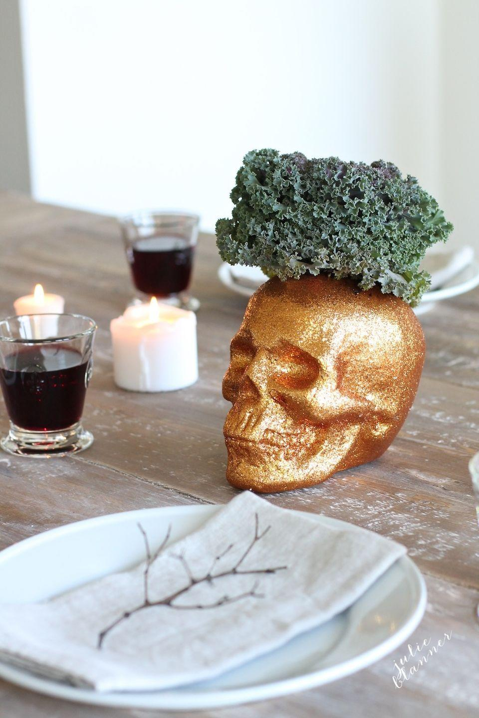"<p>They're way less scary when you top them with a flower or plant. Maybe equally as scary when stuffed with greens. That's one way to get 'em on the table! See more at <a href=""http://julieblanner.com/halloween-party-table-setting/"" rel=""nofollow noopener"" target=""_blank"" data-ylk=""slk:Julie Blanner"" class=""link rapid-noclick-resp"">Julie Blanner</a>.</p><p><a class=""link rapid-noclick-resp"" href=""https://www.amazon.com/Springfield-Leather-Company-Desert-Glitter/dp/B009SRB95Q/ref=sr_1_5?tag=syn-yahoo-20&ascsubtag=%5Bartid%7C10057.g.2554%5Bsrc%7Cyahoo-us"" rel=""nofollow noopener"" target=""_blank"" data-ylk=""slk:BUY NOW"">BUY NOW</a> <strong><em>Gold Glitter Paint, $8</em></strong></p>"