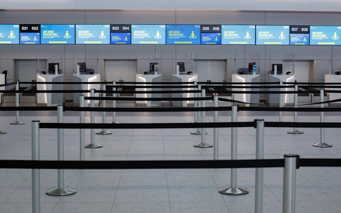 Social distancing measures sit above empty check-in desks at London Stansted Airport, - Luke MacGregor/Bloomberg