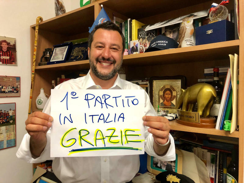 """In this photo provided by the League party press office, Italian Interior Minister, Deputy-Premier and leader of the League party, Matteo Salvini, shows a banner reading in Italian """"First party in Italy, Thanks"""", in Milan, Italy, Sunday, May 26, 2019. Italian exit polls indicate Matteo Salvini's right-wing populist League is leading Italian party in European election. (Lega via AP)"""