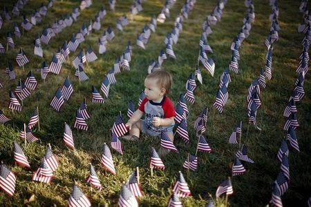Baby sits in a field of flags to honor victims of the September 11, 2001 attacks, in Santa Clarita, California