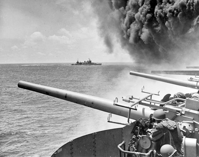 FILE - In this June 4, 1942 file photo provided by the U.S. Navy the USS Astoria (CA-34) steams by USS Yorktown (CV-5), shortly after the carrier had been hit by three Japanese bombs in the battle of Midway. Researchers scouring the world's oceans for sunken World War II ships are honing in on debris fields deep in the Pacific. A research vessel called the Petrel is launching underwater robots about halfway between the U.S. and Japan in search of warships from the Battle of Midway. (William G. Roy/U.S. Navy via AP, File)