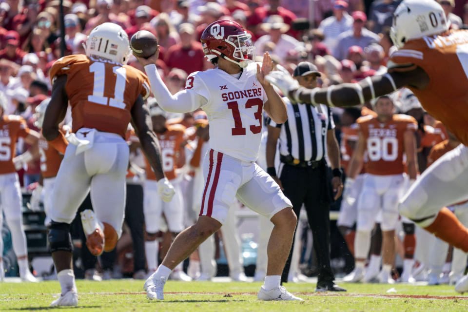 Oklahoma quarterback Caleb Williams (13) throws downfield as Texas defensive back Anthony Cook (11) closes in during the second half of an NCAA college football game at the Cotton Bowl, Saturday, Oct. 9, 2021, in Dallas. Oklahoma won 54-48. (AP Photo/Jeffrey McWhorter)
