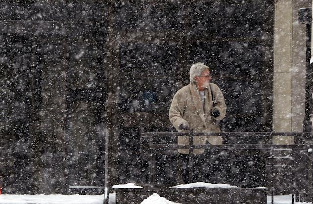 Snow continues to fall in downtown St. Joseph, Mo., as people exit the Missouri State building Tuesday, Feb. 4, 2014. (AP Photo/The St. Joseph News-Press, Todd Weddle)