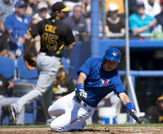 Toronto Blue Jays' Munenori Kawasaki dives for the plate to score as Pittsburgh Pirates starting pitcher Gerrit Cole runs in the background during the first inning of a spring exhibition baseball in Dunedin, Fla., Friday Feb. 28, 2014. (AP Photo/The Canadian Press, Frank Gunn)