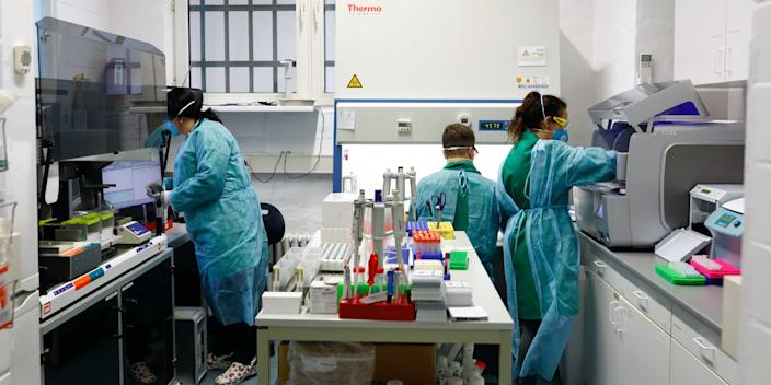 Employees in protective clothing do testings for the corona virus at a laboratory in Berlin, Germany, March 26, 2020.