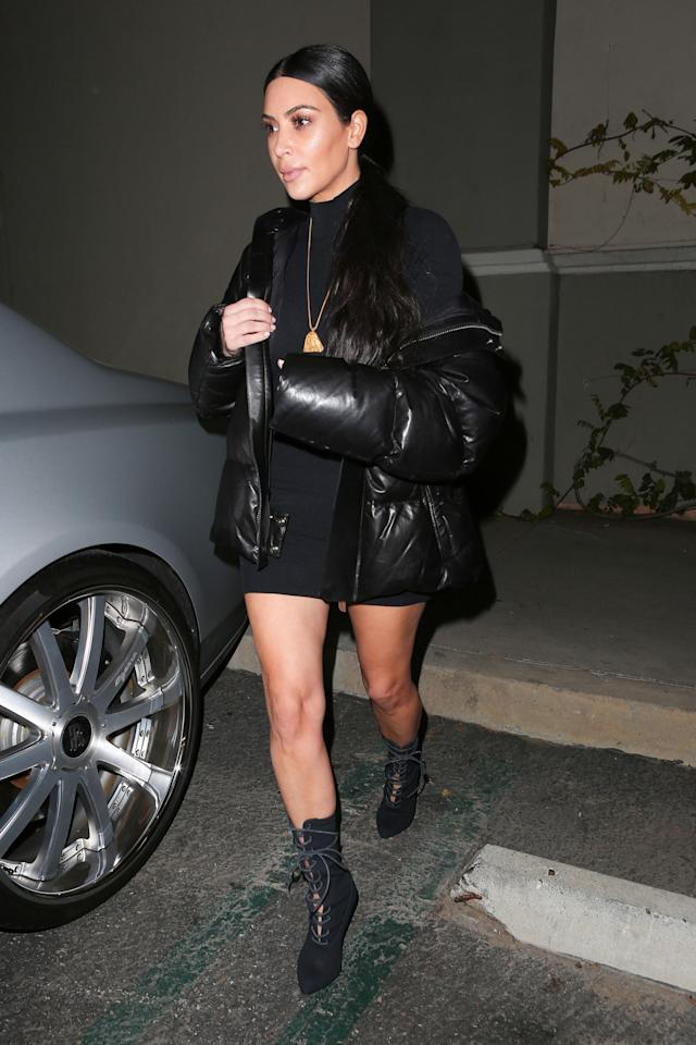 <p>In a black turtleneck minidress, puffer coat, gold pendant necklace and Yeezy lace-up ankle booties for amovie night in LA with her family and husbandKanye West.</p>