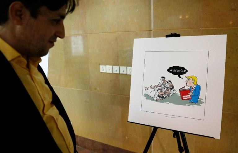 "An Iranian man looks at an illustration during the ""Persian Gulf Forever"" cartoon exhibition in Tehran on October 18, 2017"