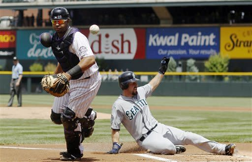 Seattle Mariners' Dustin Ackley, right, slides safely across home plate as Colorado Rockies catcher Wilin Rosario watches a bad throw get past him in the first inning of an interleague baseball game in Denver on Sunday, May 20, 2012. (AP Photo/David Zalubowski)