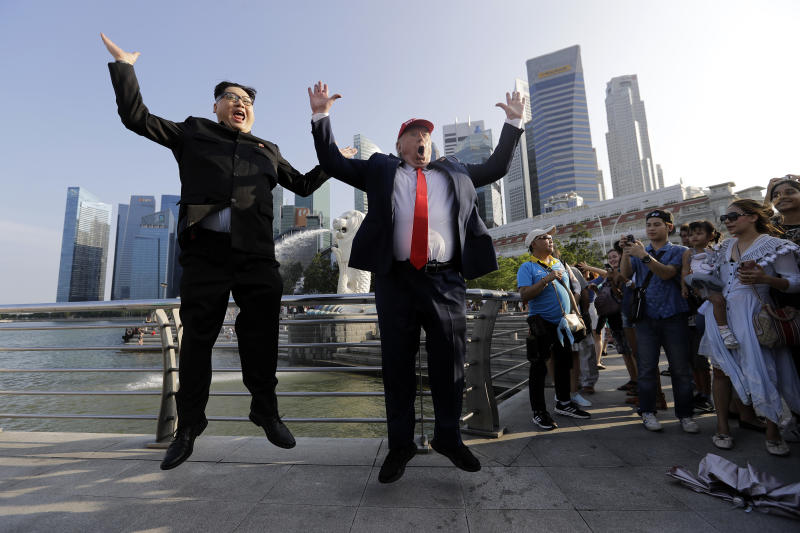 Kim Jong Un and Donald Trump impersonators, Howard X, left, and Dennis Alan, second left, pose for photographs during their visit to the Merlion Park, a popular tourist destination in Singapore, on Friday, June 8, 2018. Kim Jong Un lookalike who uses the name Howard X said he was detained and questioned upon his arrival in Singapore on Friday, days before a summit between the North Korean leader and President Donald Trump. (AP Photo/Wong Maye-E)